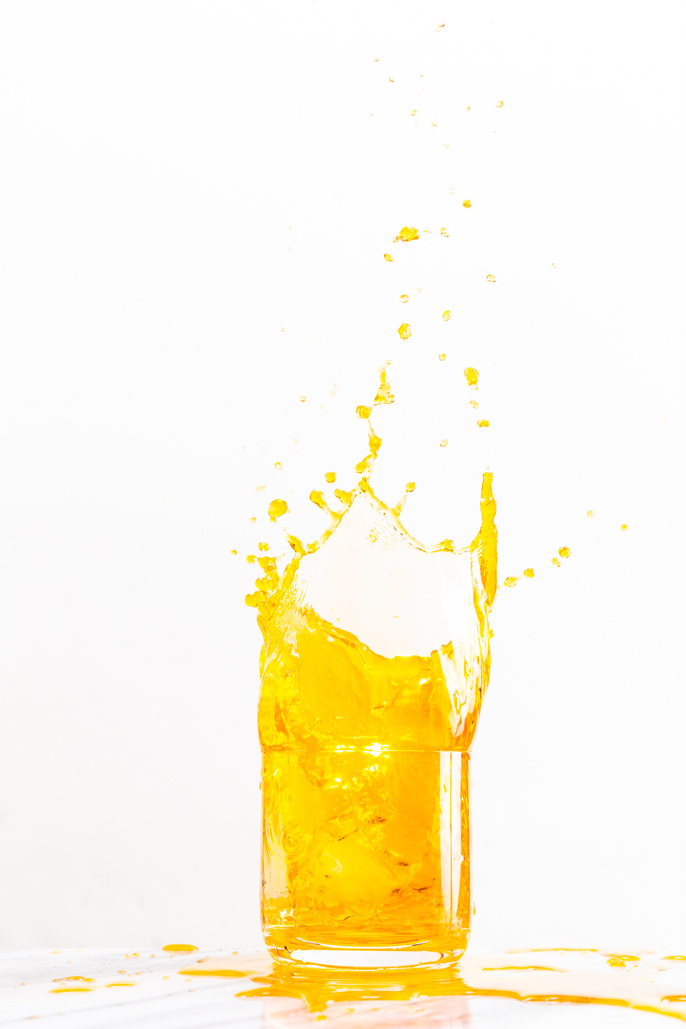 Bright yellow liquid splashes out of a glass against a white background